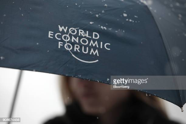 An attendee uses a 'World Economic Forum' branded umbrella during heavy snowfall ahead of the World Economic Forum in Davos Switzerland on Monday Jan...