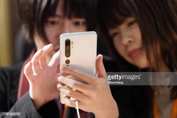 An attendee uses a Xiaomi Corp. Mi Note 10 smartphone during a news conference in Tokyo, Japan, on Monday, Dec. 9, 2019. Xiaomi, the worlds...