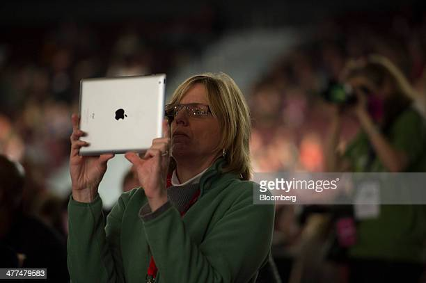 An attendee uses an Apple Inc iPad to take a photograph of Anne Wojcicki cofounder and chief executive officer of 23andMe as she speaks during a...