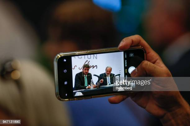 An attendee uses an Apple Inc iPhone to take a photograph of Carlos Slim chairman emeritus of America Movil SAB right speaking during a press...