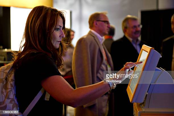 An attendee uses an Eastman Kodak Co Kodak Picture kiosk to print photographs from her Facebook account at the 2012 International Consumer...