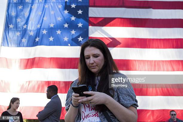 An attendee uses her mobile device while standing in front of a large American flag during a campaign event for Hillary Clinton 2016 Democratic...