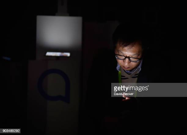 An attendee uses his electronic device after power was lost during CES 2018 inside the central hall at the Las Vegas Convention Center on January 10...