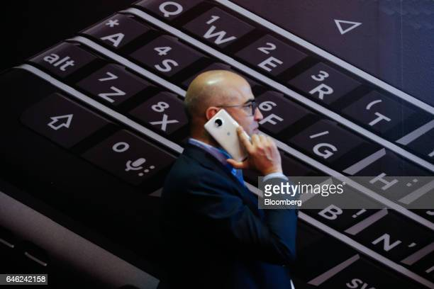 An attendee uses his mobile device as he walks past a poster for the Blackberry Keyone smart phone, manufactured by Blakberry Ltd., on the second day...