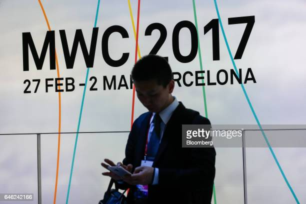 An attendee uses his mobile device on the second day of Mobile World Congress in Barcelona, Spain, on Tuesday, Feb. 28, 2017. A theme this year at...