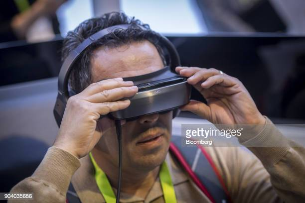 An attendee uses the Luci Immers 4K ultraHD immersionondemand headset during the 2018 Consumer Electronics Show in Las Vegas Nevada US on Thursday...