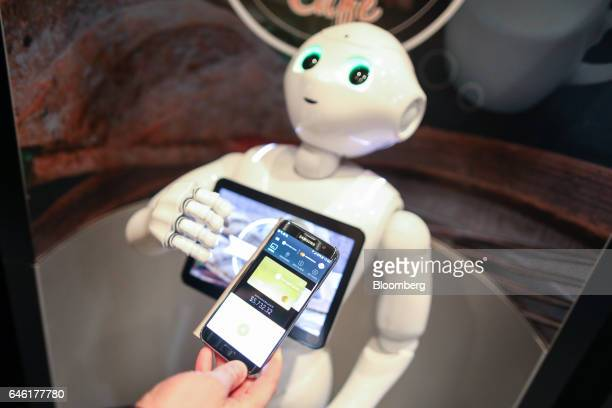 An attendee uses the Samsung Pay app on a Galaxy smartphone manufactured by Samsung Electronics Co Ltd to interact with SoftBank Group Corp's Pepper...