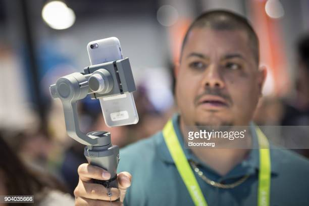 An attendee uses the SZDJITechnology Co Osmo smartphone stabilizer during the 2018 Consumer Electronics Show in Las Vegas Nevada US on Thursday Jan...