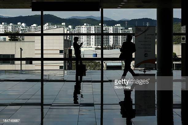 An attendee using a mobile phone is silhouetted while another walks through the venue of the 22nd World Energy Congress in Daegu South Korea on...