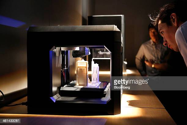 An attendee views a Makerbot Industries LLC Replicator 3D printer on display during the 2014 Consumer Electronics Show in Las Vegas Nevada US on...