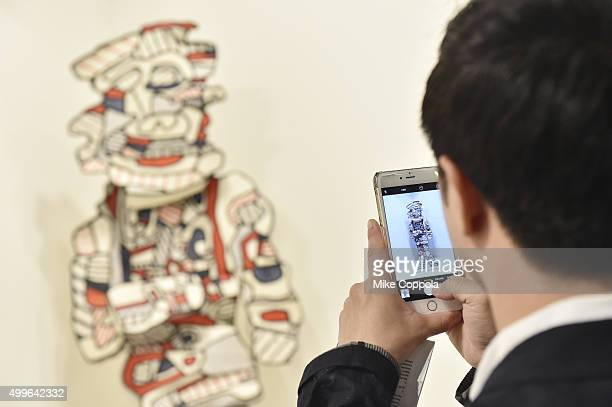 An attendee views artwork from the Helly Nahmad Gallery at the Art Basel Miami Beach VIP Preview at the Miami Beach Convention Center on December 2...