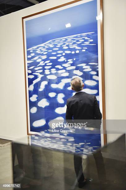An attendee views 'Dubai World I' by artist Andreas Gursky from White Cube at the Art Basel Miami Beach VIP Preview at the Miami Beach Convention...
