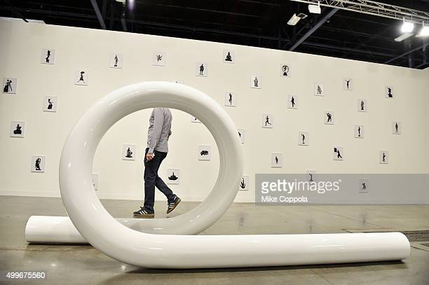 An attendee views 'Solar Feminine 2013' by artist Carol Bove at the Art Basel Miami Beach VIP Preview at the Miami Beach Convention Center on...