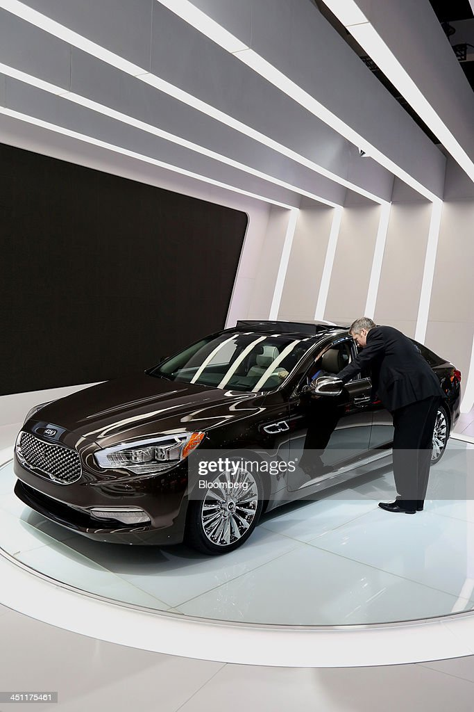 An attendee views the inside of a Kia Motors Corp. K900 V8 vehicle displayed during the LA Auto Show in Los Angeles, California, U.S., on Thursday, Nov. 21, 2013. The 2013 LA Auto Show is open to the public Nov. 22 - Dec. 1. Photographer: Jonathan Alcorn/Bloomberg via Getty Images