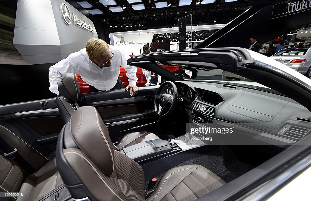 An attendee views the interior of a Daimler AG Mercedes Benz E 350 Cabriolet vehicle during the 2013 North American International Auto Show (NAIAS) in Detroit, Michigan, U.S., on Tuesday, Jan. 15, 2013. The Detroit auto show runs through Jan. 27 and will display over 500 vehicles, representing the most innovative designs in the world. Photographer: David Paul Morris/Bloomberg via Getty Images