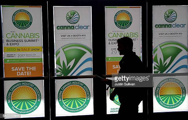 An attendee walks by windows with the logo for the 2016 Cannabis Business Summit Expo on June 22 2016 in Oakland California Policy makers and...