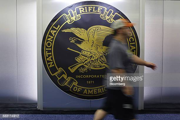 An attendee walks past a National Rifle Association logo on the exhibit floor during the annual meeting in Louisville Kentucky US on Friday May 20...