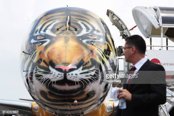An attendee walks past a prototype of the Embraer SA E190 E2 passenger aircraft on display during a media preview day at the Singapore Airshow held...