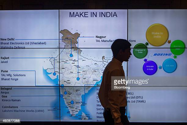 An attendee walks past a screen displaying Boeing Co's Indian manufacturing partners on a map as part of The Make In India program at the India's...