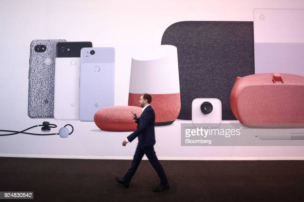 An attendee walks past an advertising board displaying Google Inc Home products during day two of the Mobile World Congress in Barcelona Spain on...