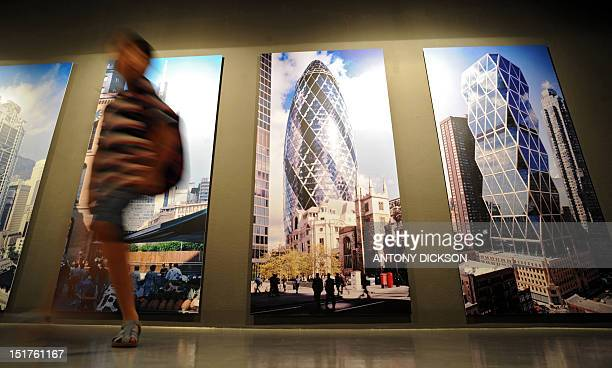 An attendee walks past photographs of the Hearst Corporation headquarters in New York and the Swiss Re Headquarters in London during an exhibition...