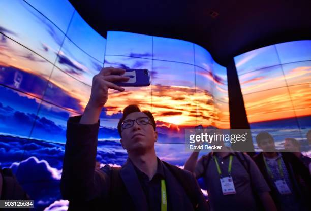 An attendee walks through LG's televison display at the LG booth during CES 2018 at the Las Vegas Convention Center on January 9 2018 in Las Vegas...