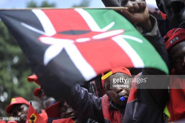 An attendee waves a Kenyan flag during a presidential election rally for the Jubilee Party in Nairobi Kenya on Friday Aug 4 2017 The winner of...