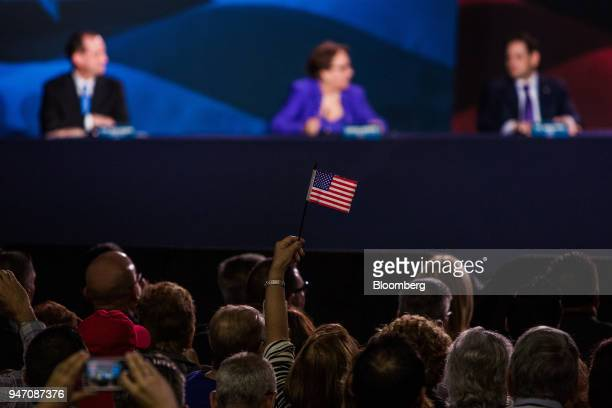 An attendee waves an American flag during a roundtable discussion with US President Donald Trump not pictured on tax cuts for Florida small...