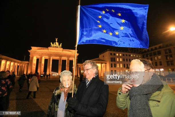 """An attendee waves an European Union flag during a flashmob gathering at Brandenburg Gate, to sing the """"Anthem of Europe"""" to mark the moment the U.K...."""