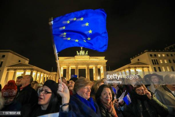 An attendee waves an European Union flag during a flashmob gathering at Brandenburg Gate to sing the Anthem of Europe to mark the moment the UK left...