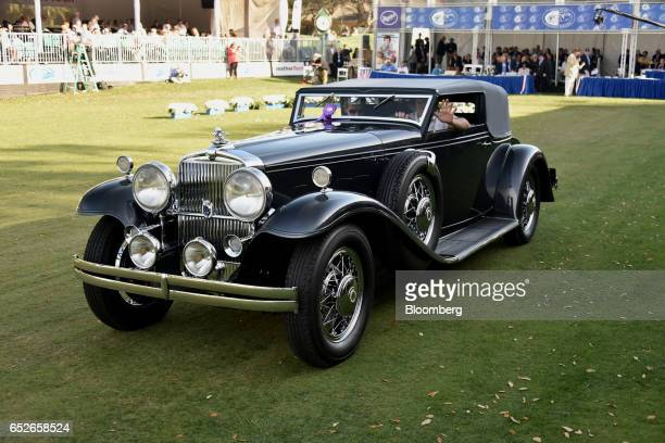 An attendee waves while driving in a 1931 Stutz DV 32 LeBaron Convertible Victoria luxury vehicle during the 2017 Amelia Island Concours d'Elegance...