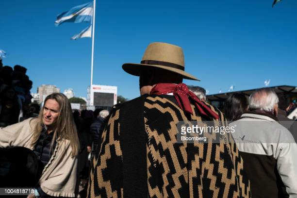 An attendee wearing a cowboy hat and poncho walks in front of an Argentinian national flag during La Exposicion Rural agricultural and livestock show...