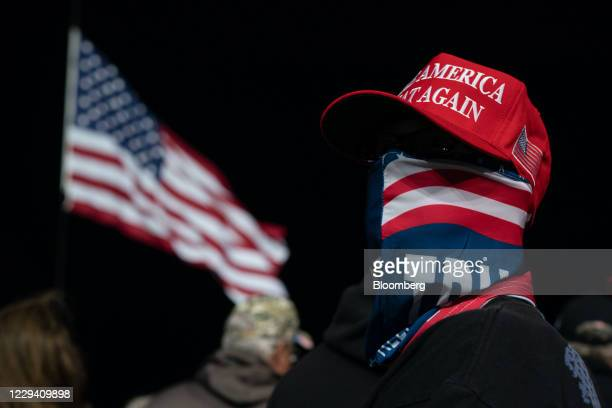 An attendee wearing a hat and scarf waits for the arrival of U.S. President Donald Trump during a campaign rally in Rome, Georgia, U.S., on Sunday,...