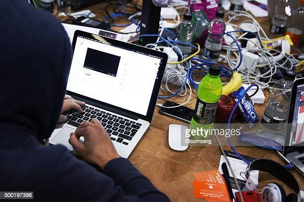 An attendee wearing a hooded top and working on an Apple Inc laptop computer participates in the TechCrunch Disrupt London 2015 Hackathon in London...