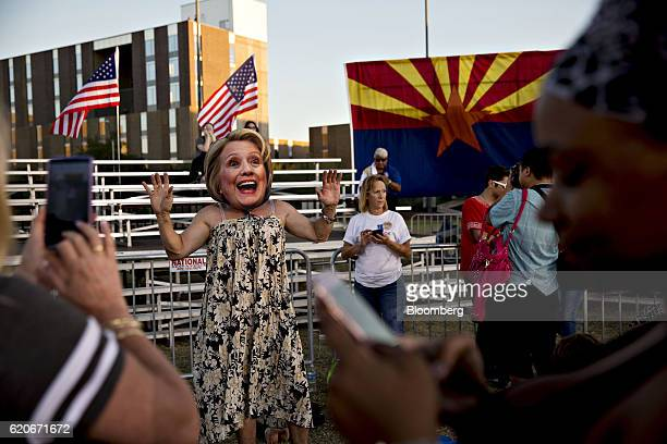 An attendee wearing a mask depicting Hillary Clinton, 2016 Democratic presidential nominee, poses for photographs near an Arizona state flag in...