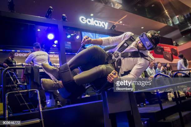 An attendee wearing a Samsung Electronics Co Gear virtual reality headset rides the Flying Dino simulator during the 2018 Consumer Electronics Show...