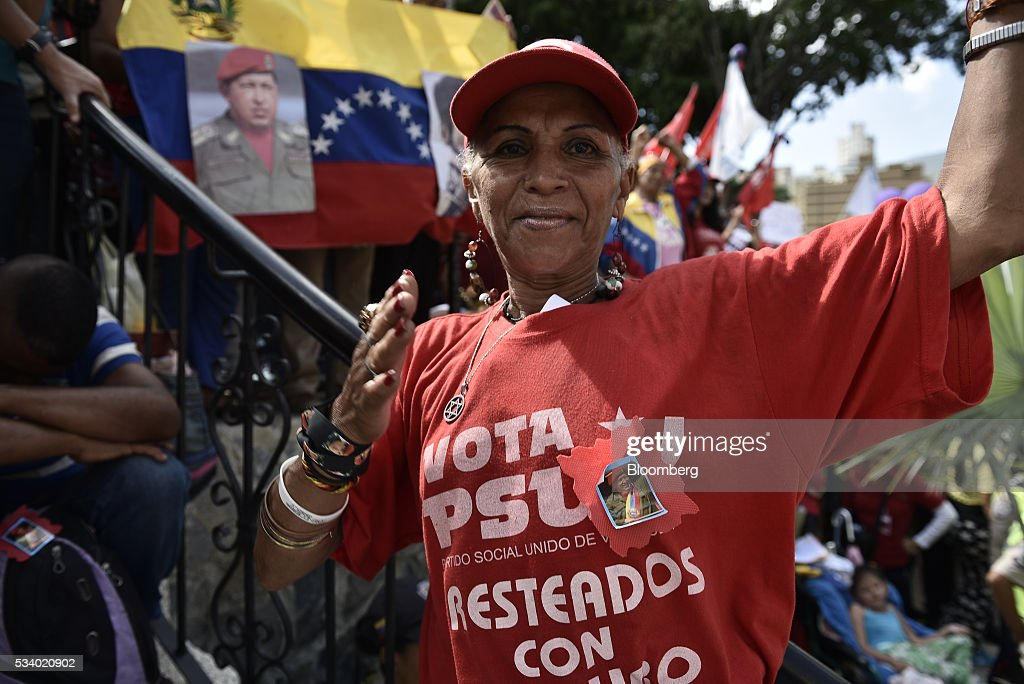 An attendee wearing a United Socialist Party of Venezuela (PSUV) t-shirt stands for a photograph during a rally for women and peace at the Miraflores Palace in Caracas, Venezuela on Tuesday, May 24, 2016. On Tuesday, hundreds of women took to the streets in a show of support for President Maduro and against what they called the violent demonstrations by the opposition. Photographer: Carlos Becerra/Bloomberg via Getty Images