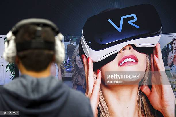 An attendee wearing a virtual reality headset watches a preview of an adult video produced by Naughty America VR in front of a promotional banner...