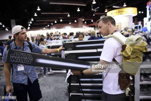An attendee wearing a Yoda backpack browses Star Wars lightsabers displayed for sale at a store during the D23 Expo 2017 in Anaheim California US on...