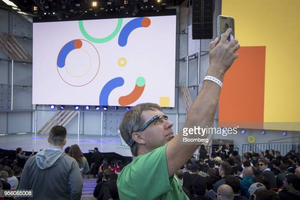 An attendee wearing Google Glass glasses takes a photograph with a smartphone before the Google I/O Developers Conference in Mountain View California...