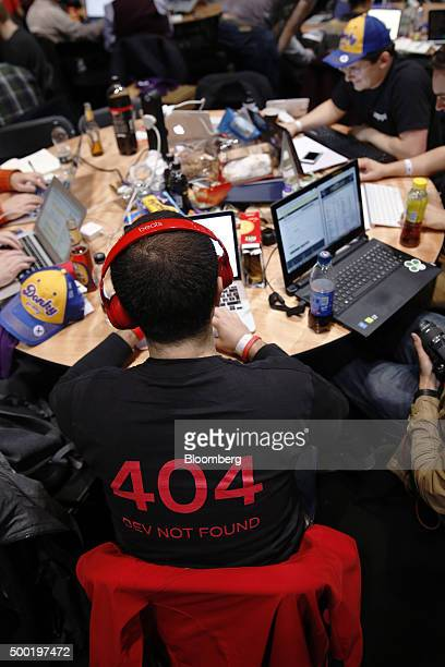 An attendee wearing headphones and a shirt with '404 DEV NOT FOUND' printed on it and working on a laptop computer participates in the TechCrunch...