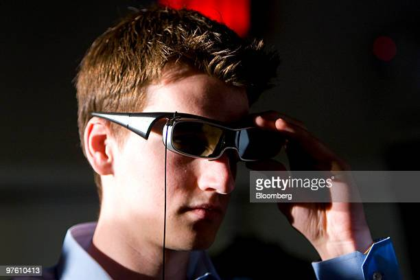 An attendee wears 3D active shutter glasses in front of a new Panasonic Corp Viera full HD 3D 50 inch television during a launch event at a Best Buy...