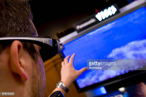 An attendee wears 3D active shutter glasses while watching effects on a new Panasonic Corp Viera full HD 3D 50 inch television during a launch event...