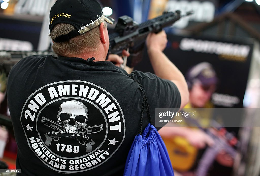 An attendee wears a 2nd amendment shirt while inspecting an assault rifle during the 2013 NRA Annual Meeting and Exhibits at the George R. Brown Convention Center on May 5, 2013 in Houston, Texas. More than 70,000 people attended the NRA's 3-day annual meeting that featured nearly 550 exhibitors, a gun trade show and a political rally.