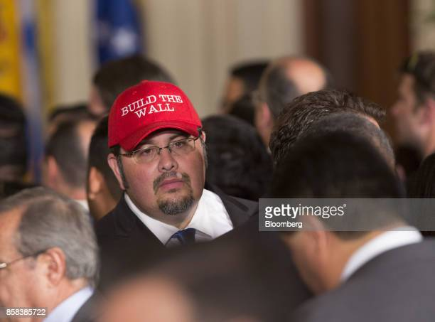 An attendee wears a 'Build The Wall' hat during an Hispanic Heritage month event with US President Donald Trump not pictured at the White House in...