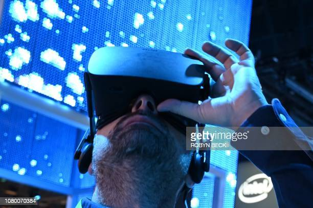 An attendee wears a Genius VR headset at the Intel booth during CES 2019 consumer electronics show January 10 2019 at the Las Vegas Convention Center...