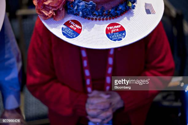 An attendee wears a hat displaying Donald Trump campaign stickers during a prayer at the Conservative Political Action Conference in National Harbor...