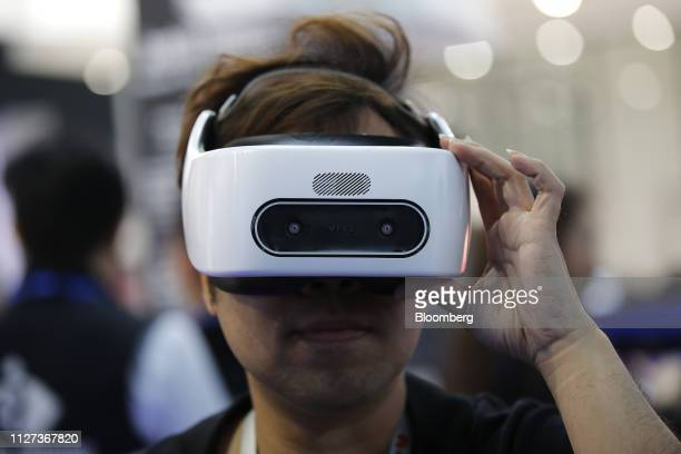 An attendee wears a HTC Corp Vive Focus Plus virtual reality headset on the opening day of the MWC Barcelona in Barcelona Spain on Monday Feb 25 2019...