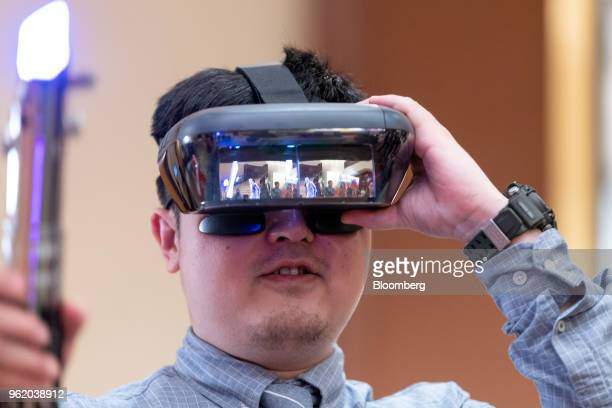 An attendee wears a Lenovo Group Ltd augmented reality headset while playing the 'Star Wars Jedi Challenges' game at a news conference in Hong Kong...