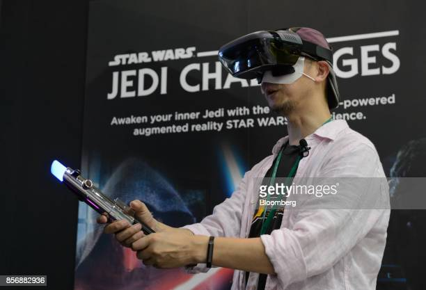 An attendee wears a Lenovo Mirage AR headset and holds a Lightsaber controller while playing the Star Wars Jedi Challenges video game developed by...